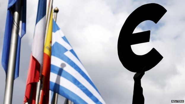 A Greek flag flies behind a statue to European unity outside the EU Parliament in Brussels