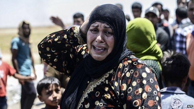 A Syrian woman cries after a US-led coalition air strike on IS militants in Tal Abyad (14 June 2015)