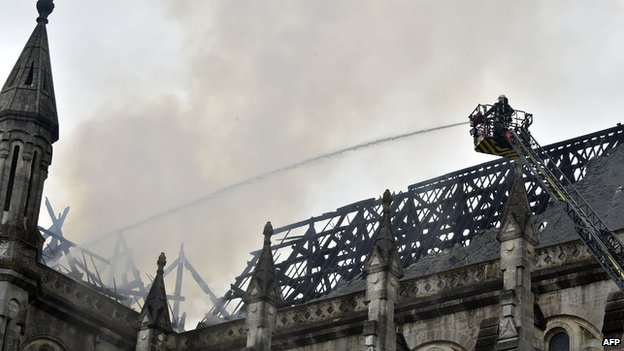 Firefighters works after a spectacular blaze that ravaged the roof of a 19th century basilica in Nantes, western France on june 15, 2015.