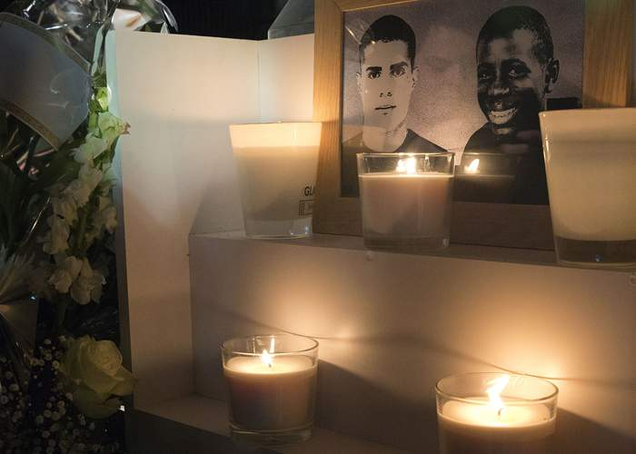 Flowers and candles placed near a plaque in Clichy-sous-Bois in memory of Bouna Traore (right) and Zyed Benna