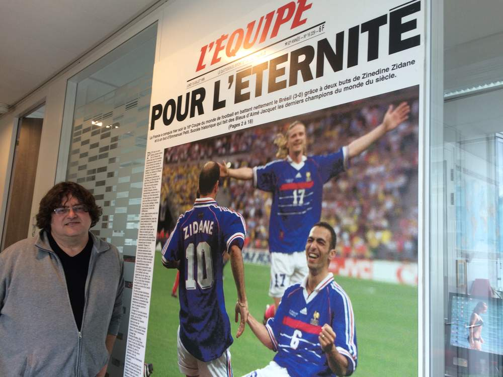 Vincent Duluc, posing in front of L'Equipe's front-page coverage of France's '98 World Cup win