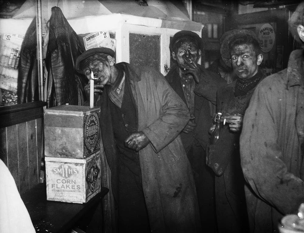 1936: South Wales miners, forbidden from carrying matches, light up in the tobacconist's