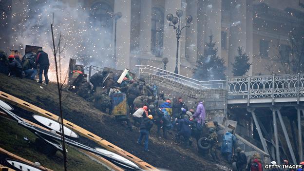 Protesters climb the side of a bridge
