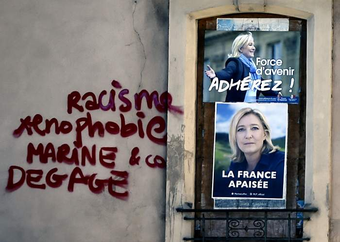 """""""Racism, xenophobia, Marine and co, clear off!""""Graffiti next to FN posters in southern France, 2016(Getty Images)"""