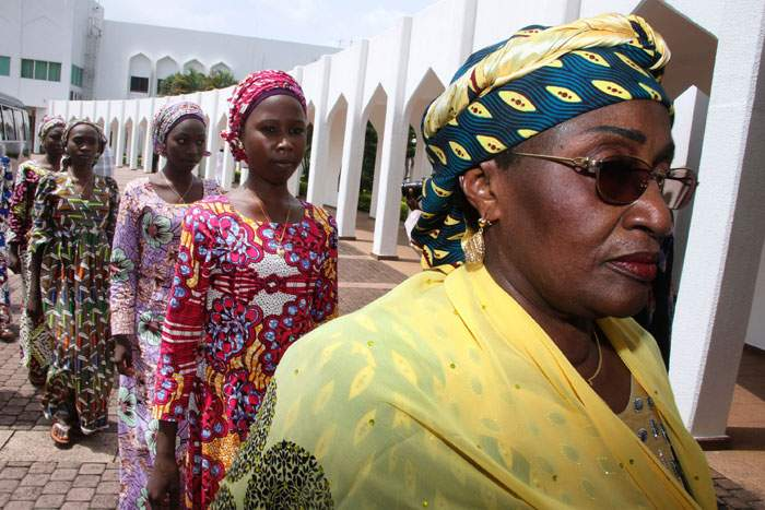 Women's Affairs Minister Aisha al-Hassan leads the 21 girls released in October 2016 to a meeting with Nigeria's president
