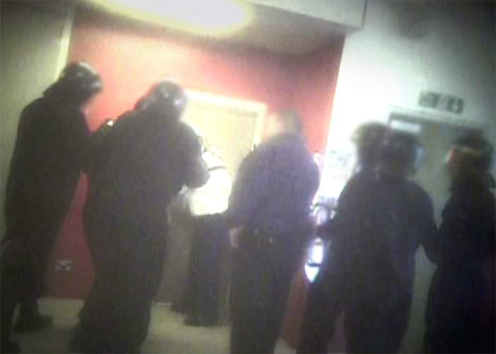 Officers in riot gear prepare to enter a room