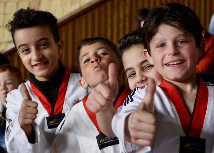 Children in Damascus give a thumbs during a break from competing in a regional taekwondo competition